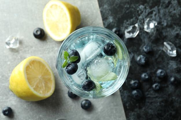 Szklanka letniego koktajlu i składników na dwukolorowym tle