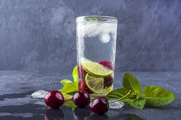 Szklanka letniej lemoniady lub mrożonej herbaty. orzeźwiający chłodny napój detoksykujący z wiśnią i miętą na ciemnym tle.
