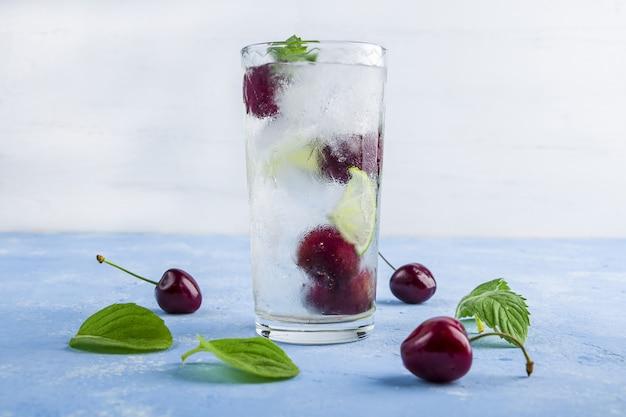 Szklanka letniej lemoniady lub mrożonej herbaty. orzeźwiający napój detox z wiśnią i miętą