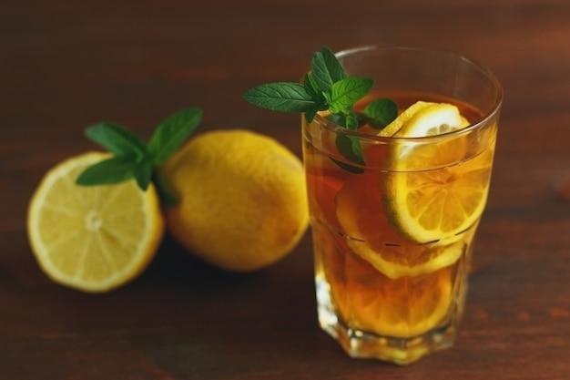 Szklanka lodowej herbaty cytrynowej z miętą na drewnianym tle domowej roboty letni napój z miejscem na kopię