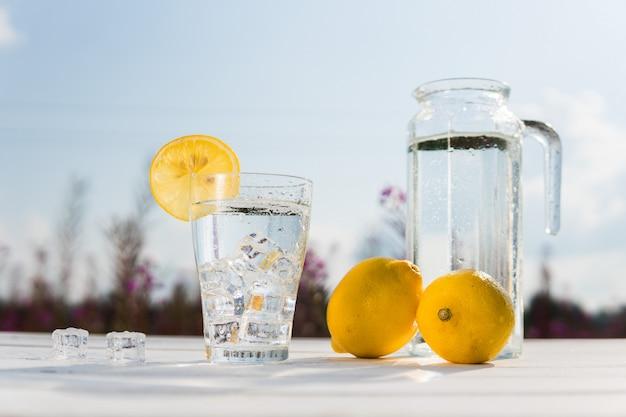 Szklanka lodu i wody ozdobiona plasterkiem cytryny stojącej na białym stole przed karafką