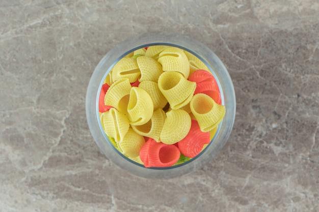 Szklanka makaronu kolorowe muszle na powierzchni marmuru.
