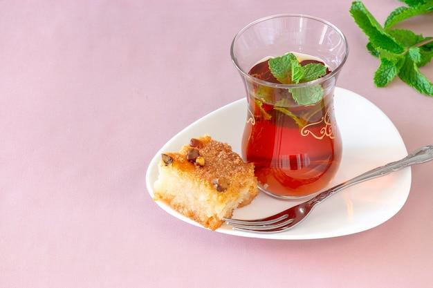 Szklanka marokańskiej miętowej herbaty z tradycyjnym arabskim ciastem z semoliny basbousa (namoora) z orzechami migdałowymi i syropem. skopiuj miejsce. selektywna ostrość. różowe tło.