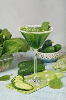 Szklanka martini wypełniona świeżym zielonym koktajlem ze szpinaku i ogórka na jasnoniebieskim tle drewnianych. napoje bezalkoholowe. zdrowa żywność i koncepcja wegetariańska.