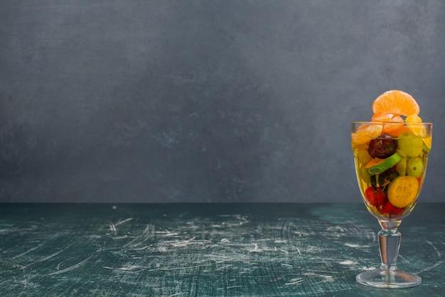 Szklanka mieszanych owoców na marmurowym stole.