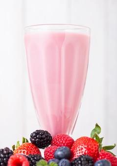 Szklanka mleczna ze świeżym letnim koktajlem z jagodami na drewnianym stole. truskawki i maliny z jagodami i jeżynami.