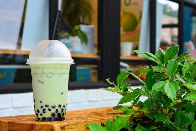 Szklanka mlecznej zielonej herbaty matcha z perełkami tapioki na drewnianym stole z zielonymi liśćmi
