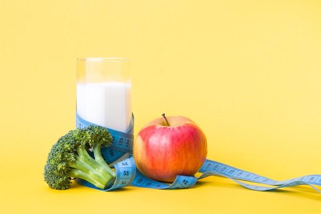 Szklanka mleka, brokuły, niebieska miarka i czerwone jabłko