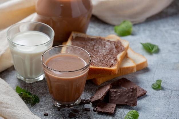 Szklanka mleka czekoladowego na ciemnej powierzchni.