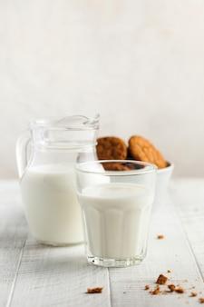 Szklanka mleka, dzbanek mleka, ciasteczka na jasnej ścianie. pojęcie produktów mlecznych, wykorzystanie mleka, produkty rolne, dzień mleczny.