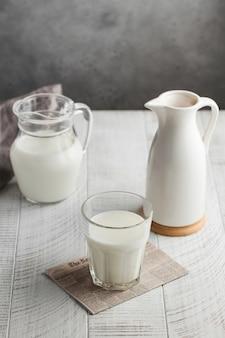 Szklanka mleka, dzbanek mleka na szarej ścianie. pojęcie mleka, wykorzystanie produktów mlecznych, produkty rolne. minimalizm. skopiuj miejsce. pionowe zdjęcie żywności.