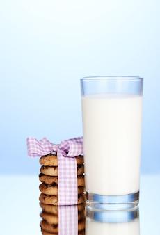 Szklanka mleka i ciasteczek na niebieskim tle