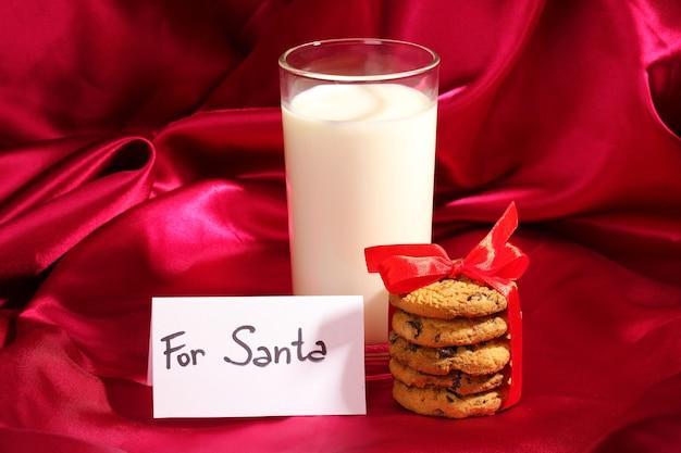 Szklanka mleka i ciasteczek na tle czerwonego sukna