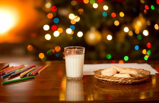 Szklanka mleka i ciasteczka czekają na świętego mikołaja w wigilię