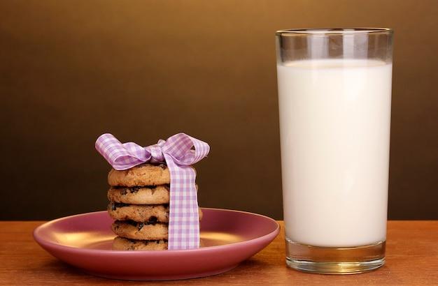 Szklanka mleka i ciasteczka na drewnianym stole na brązowej powierzchni