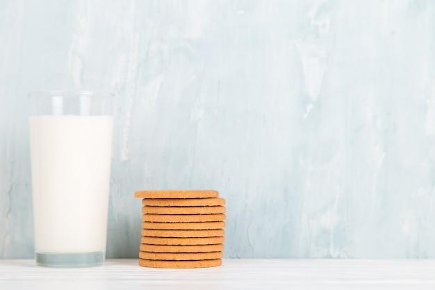 Szklanka mleka i ciasteczka na stole, na niebiesko, minimalizm. skopiuj miejsce.