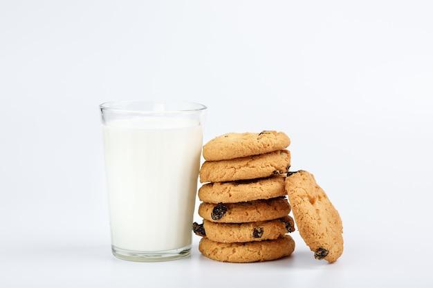 Szklanka mleka i ciasteczka z rodzynkami na białym tle