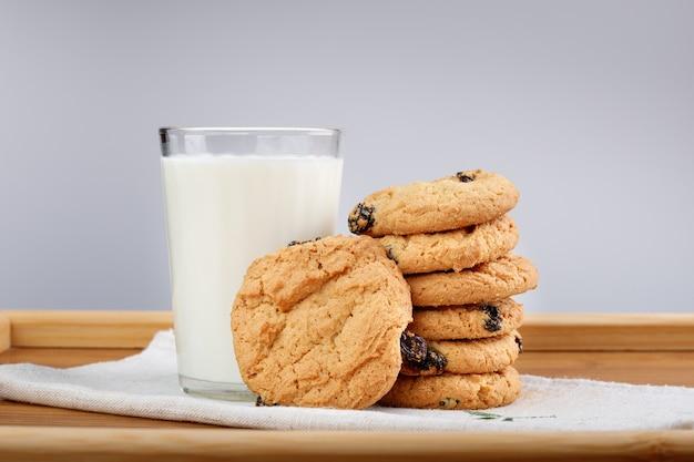 Szklanka mleka i ciasteczka z rodzynkami na drewnianej tacy