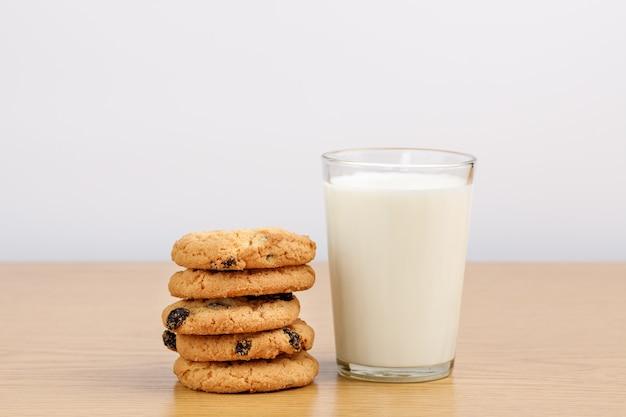 Szklanka mleka i ciasteczka z rodzynkami na stole