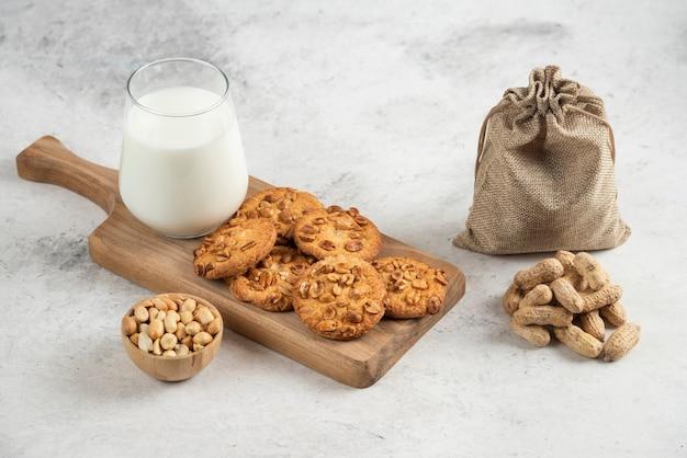 Szklanka mleka i ciastek na drewnianej desce do krojenia z orzeszkami ziemnymi.