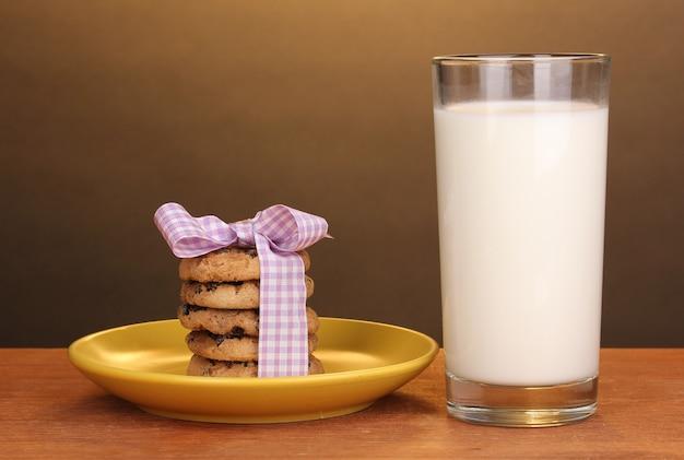Szklanka mleka i ciastek na drewnianym stole na brązowym tle