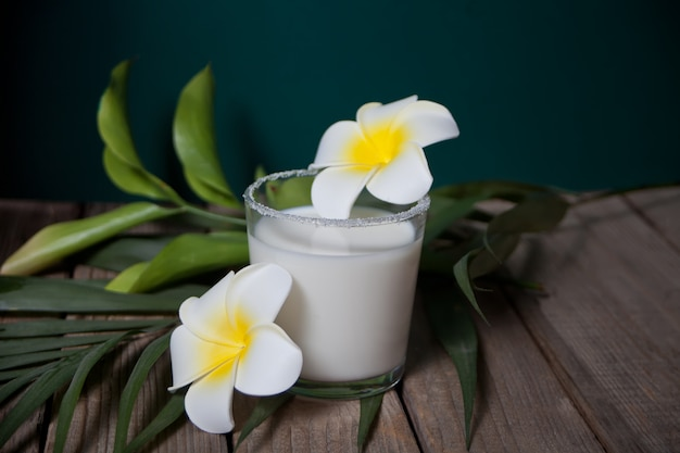 Szklanka mleka kokosowego z kwiatami plumeria i liści palmowych na drewnie