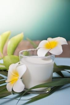 Szklanka mleka kokosowego z kwiatami plumeria i liściem palmowym