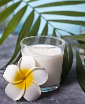 Szklanka mleka kokosowego z kwiatem plumeria i liściem palmowym