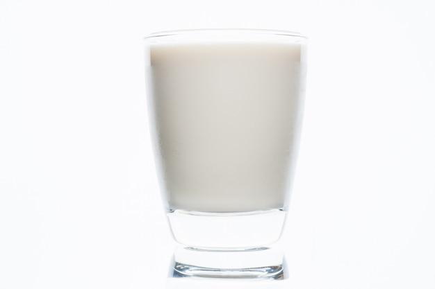 Szklanka mleka na białym tle na białej ścianie, zdrowe picie i wapniowy napój krowy