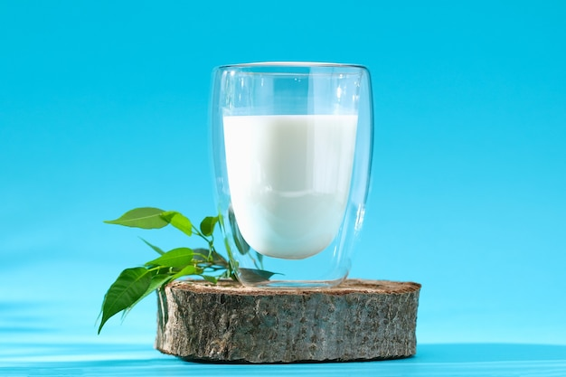 Szklanka mleka na drewnianym podium na niebieskim tle