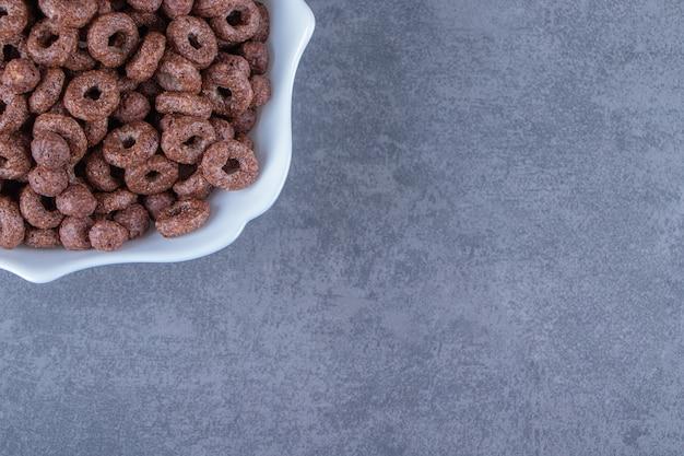 Szklanka mleka obok krążków kukurydzianych w misce, na marmurowym tle. zdjęcie wysokiej jakości