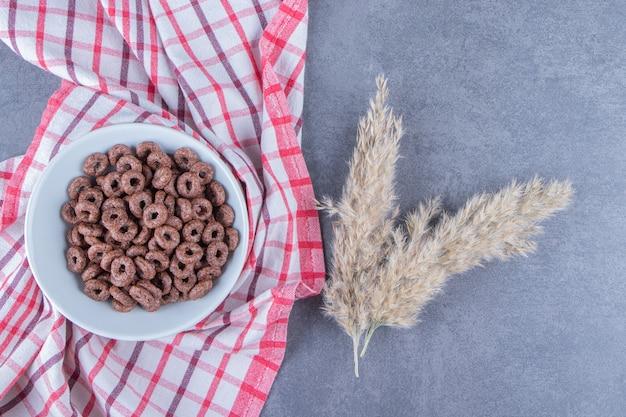 Szklanka mleka obok krążków kukurydzianych w szklanej misce obok trawy pampasowej na ściereczce, na marmurowym tle. zdjęcie wysokiej jakości