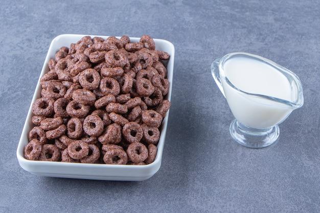 Szklanka mleka obok krążków kukurydzy w szklanej misce, na marmurowym tle. zdjęcie wysokiej jakości