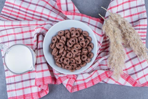 Szklanka mleka obok krążków kukurydzy w szklanej misce obok trawy pampasowej na ściereczce, na marmurowym stole.