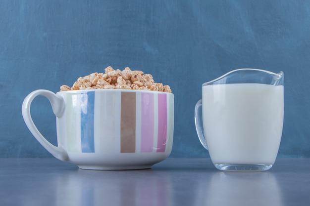 Szklanka mleka obok płatków kukurydzianych w filiżance, na marmurowym tle.