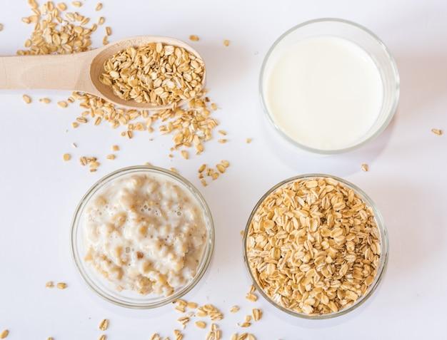 Szklanka mleka, płatków owsianych i owsianki w talerzu na białej powierzchni. widok z góry.
