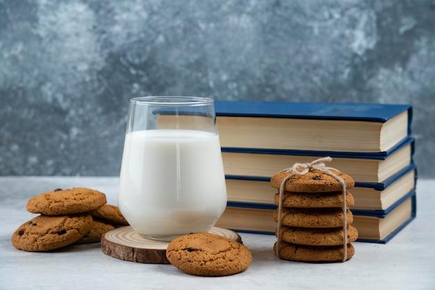 Szklanka mleka, słodkie ciasteczka i książka na marmurowym stole.