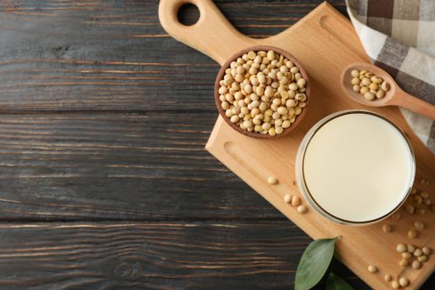 Szklanka mleka sojowego i nasion soi na drewnianym stole. widok z góry