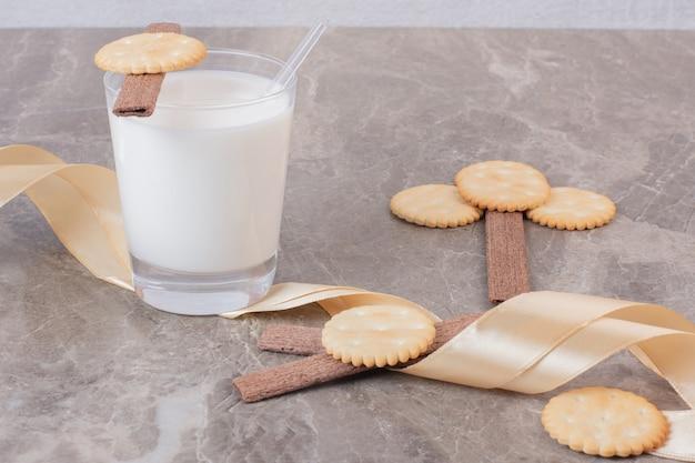 Szklanka mleka z ciastkami i wstążką na marmurowym stole.