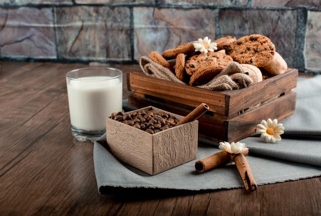 Szklanka mleka z tacą ciasteczka i pudełko z ziaren kawy na drewnianym stole
