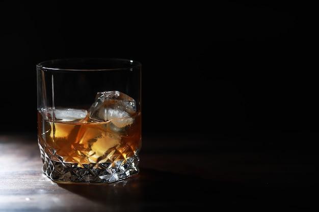 Szklanka mocnego napoju alkoholowego z lodem na drewnianym blacie barowym. whisky z kostkami lodu. szkło z schłodzonym napojem.