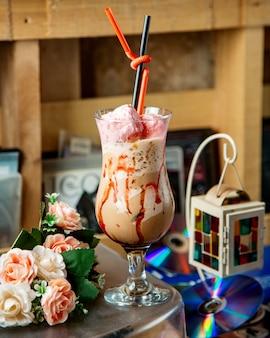 Szklanka mrożonego napoju kawowego ozdobiona różową słodką bawełną