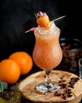 Szklanka mrożonego pomarańczowego koktajlu przyozdobionego skórką pomarańczową w kształcie truskawki