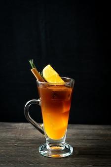 Szklanka mrożonej czarnej kawy americano i warstwa soku pomarańczowo-cytrynowego ozdobiona rozmarynem i cynamonem