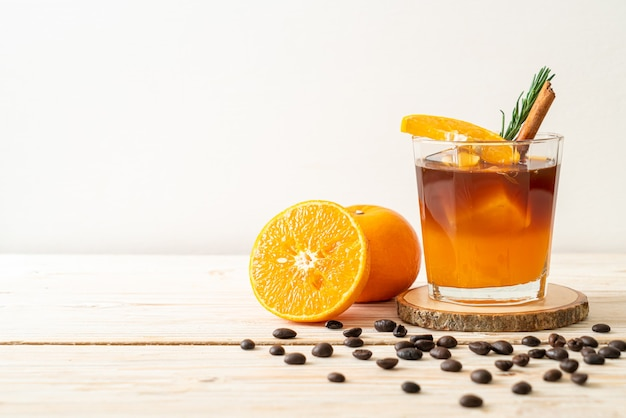 Szklanka mrożonej czarnej kawy americano i warstwa soku z pomarańczy i cytryny ozdobiona rozmarynem i cynamonem na tle drewna