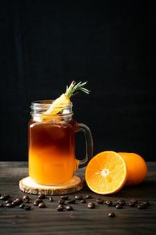 Szklanka mrożonej czarnej kawy americano i warstwa soku z pomarańczy i cytryny ozdobiona rozmarynem i cynamonem