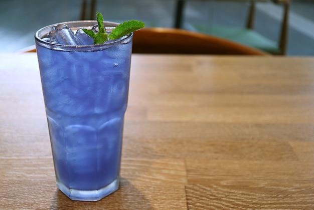 Szklanka mrożonej herbaty kwiat grochu motyla na drewnianym stole
