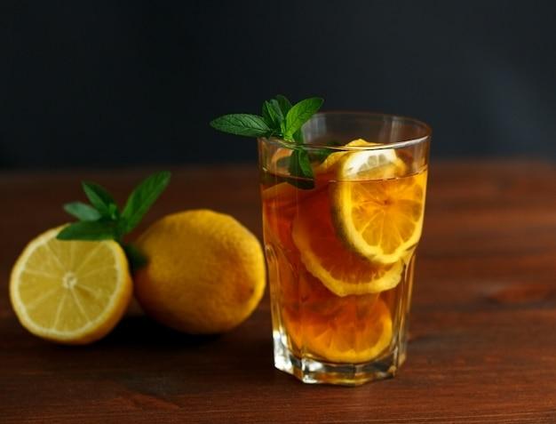 Szklanka mrożonej herbaty z plasterkami cytryny i miętą na powierzchni drewna
