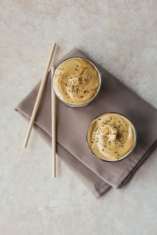 Szklanka mrożonej kawy dalgona, modnej puszystej kremowej bitej kawy i mleka na jasnobeżowym tle.