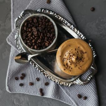 Szklanka mrożonej kawy dalgona, modnej puszystej kremowej bitej kawy i mleka na szaro.